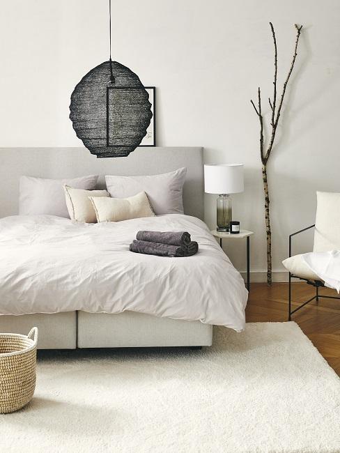 dormitorio moderno en blanco con lámpara negra y rama