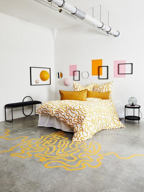 dormitorio industrial amarillo con cuadros