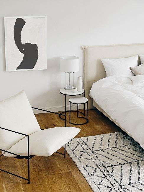 dormitorio nórdico en blanco y beige con detalles negros mesilla sillón cuadro y alfombra