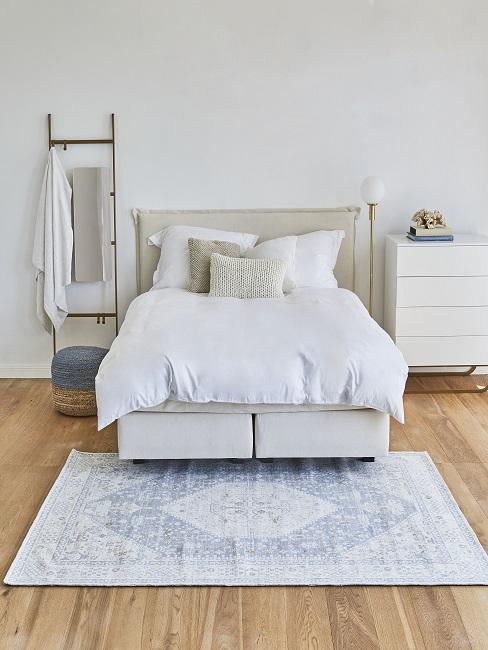 dormitorio nórdico blanco y beige con alfombra azul