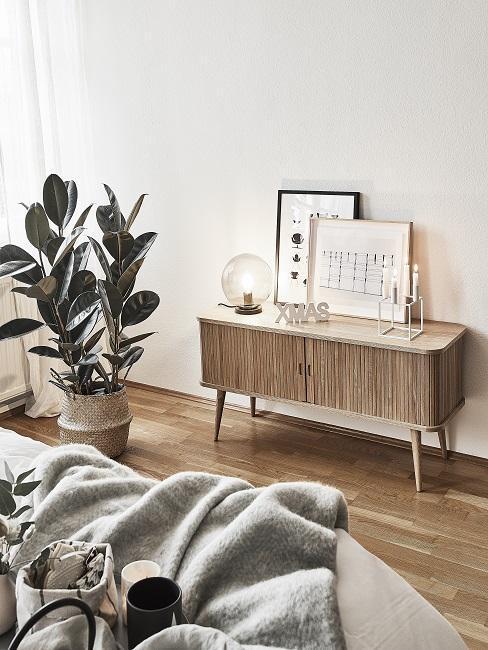 dormitorio nórdico con cómoda de madera y planta