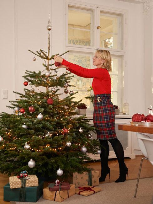 mujer decora el árbol de navidad