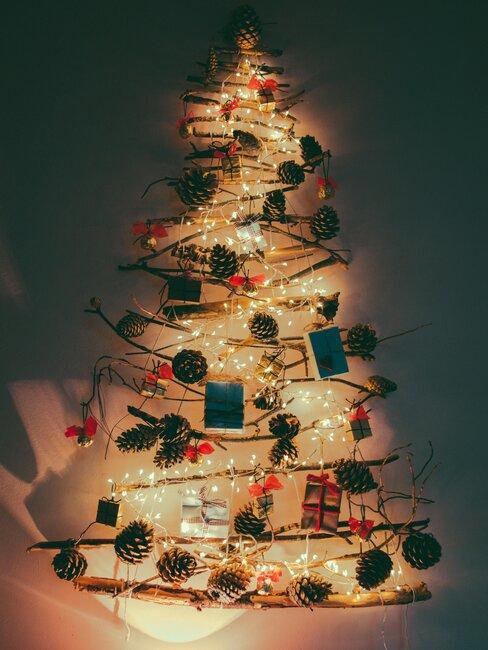 arbol de navidad hecho con palitos, luces y pinones
