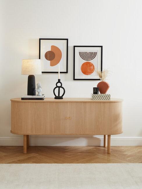 consola de madera con vela lámpara y cuadros tonos naranjas