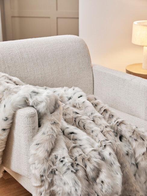 sillón beige con manta de pelo