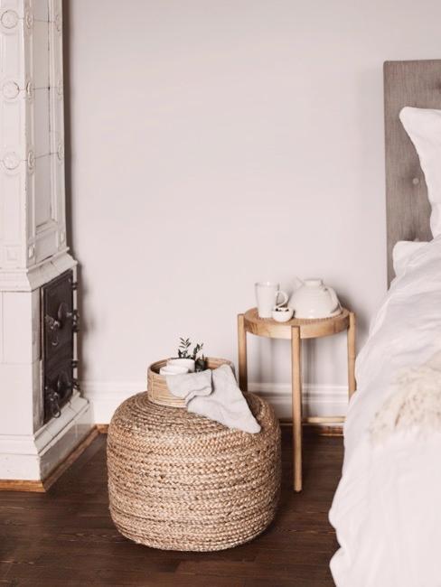 Pouf en rotin et petite table de chevet en bois avec une théière au dessus et un lit à côté
