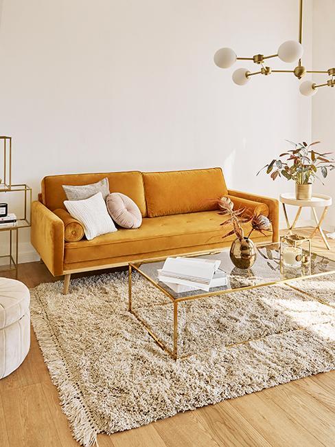 salon rétro avec un canapé jaune en velors, tapis beige, table transparente et doré