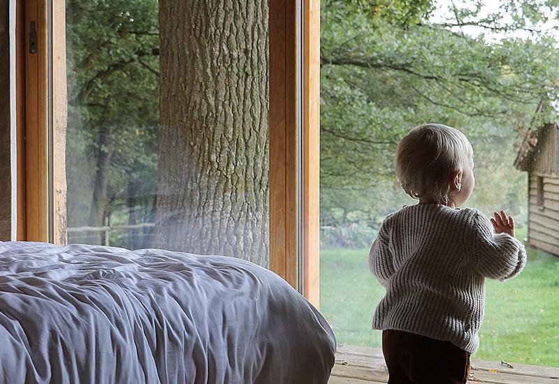 bébé debout qui regarde pas la fenêtre