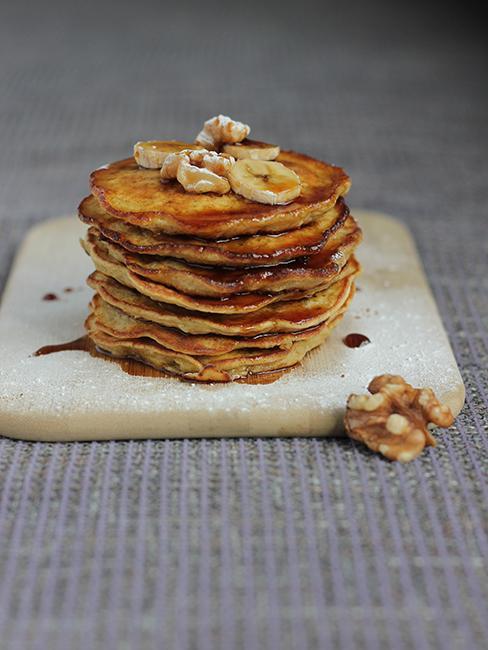 une pile de banana pancakes dressée sur une planche