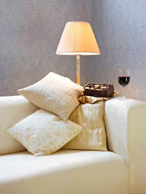 canapé blanc creme, coussins blanc-creme, lampe a poser blanc-creme, verre de vin rouge et boite de chocolats poses sur le bord du canape
