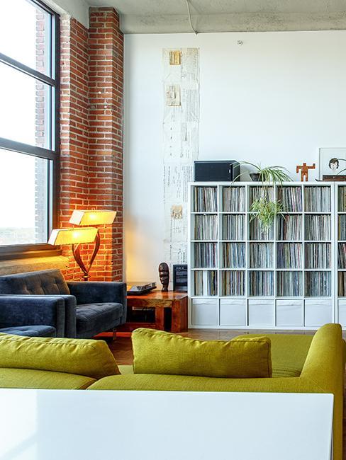 Salon dans loft avec canapé vert, fauteuil gris et grande bibliothèque