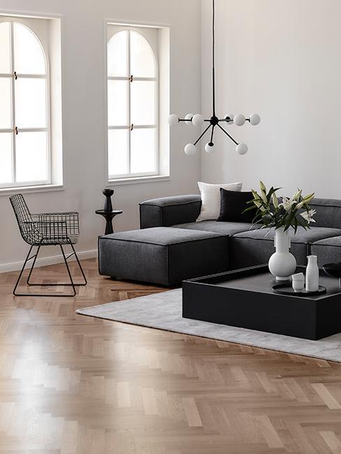 Salon dans loft avec canapé gris, chaise en métal, suspension industrielle