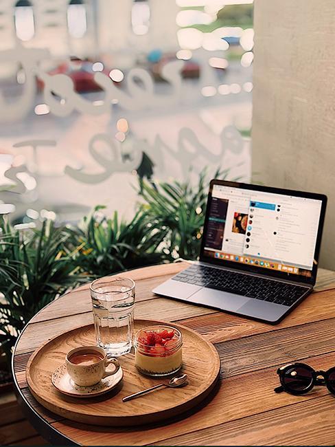 intérieur café avec table en bois, ordinateur portable et plateau rond avec café