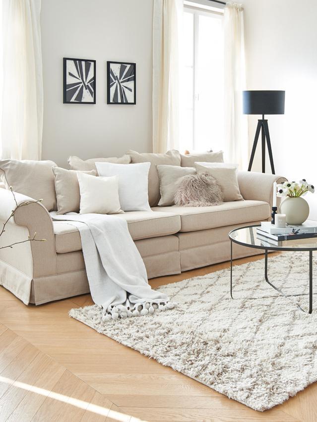 Salon rustique avec canapé crème, tapis beige et plaid blanc