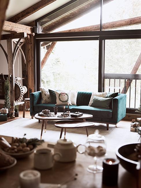 Salon rustique avec canapé vert sapin et tables basses en bois dans un chalet