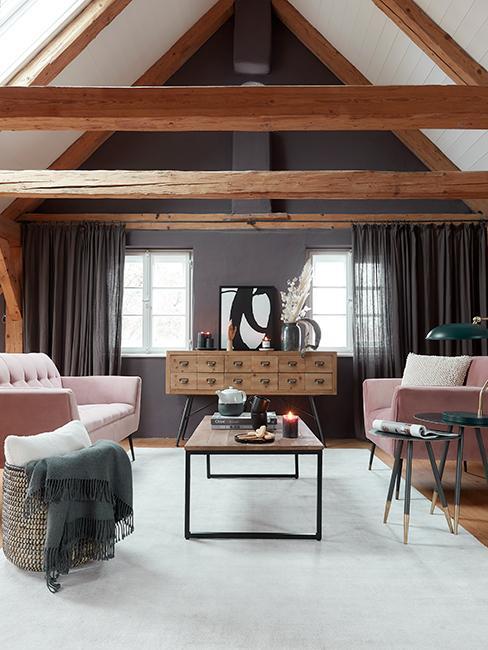 Salon chic avec canapé rose, table basse en bois, commode en bois style industriel et poutres apparentes