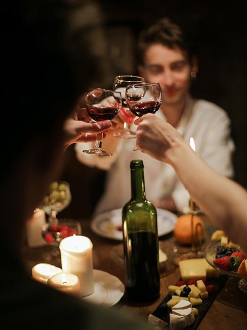 Des personnes entrain de trinquer avec des verres de vin rouge