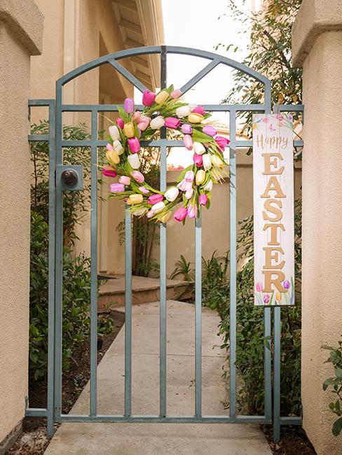 couronne de fleurs accrochée sur une grille en décoration de paques extérieur