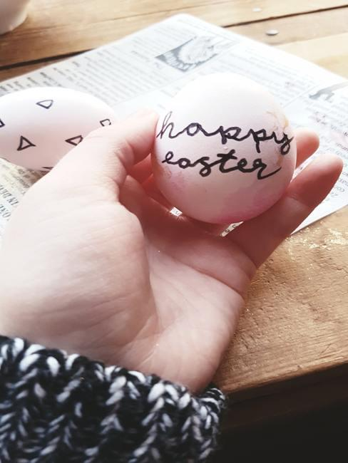 Oeuf tenu dans une main d'enfant avec écrit en noir happy easter