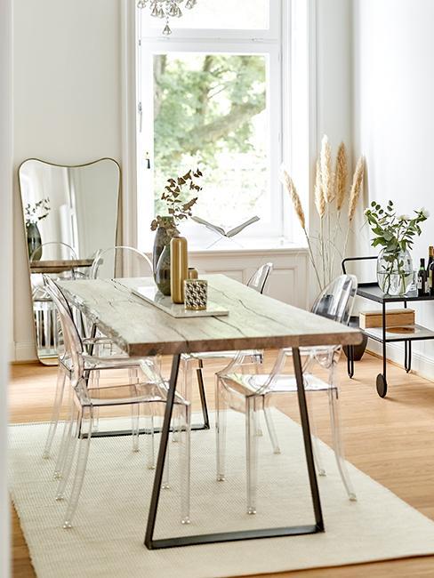 Salle à manger moderne avec une grande table en bois, des chaises tansparentes, un miroir doré et une desserte