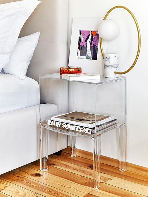 Table de chevet transparente avec livres et objets décoratifs dans une chambre