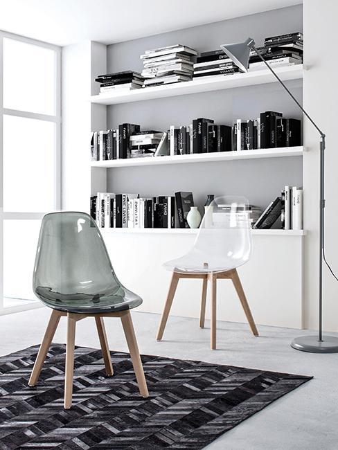 deux chaises en plexiglas devant une binliothèque