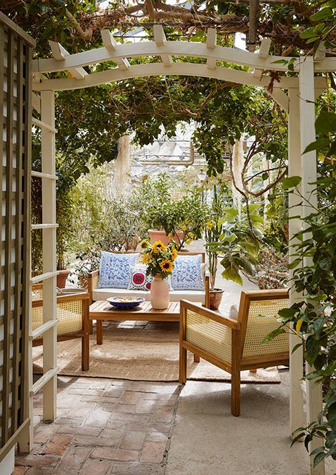 salon de jardin en bois dans une serre avec plantes vertes et vase avec tournesol