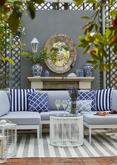 salon de jardin bleu avec table d'appoint ronde avec verre de vin, mur avec miroir et cheminée