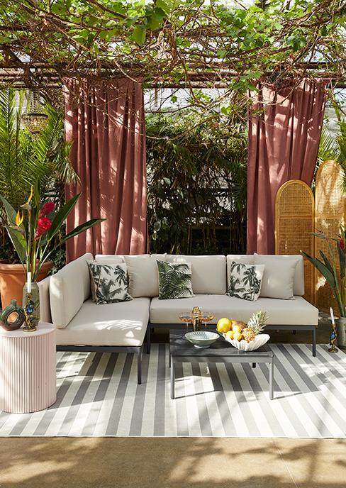 salon de jardin gris avec tapis extérieur rayé, coussins tropicaux et paravent en osier