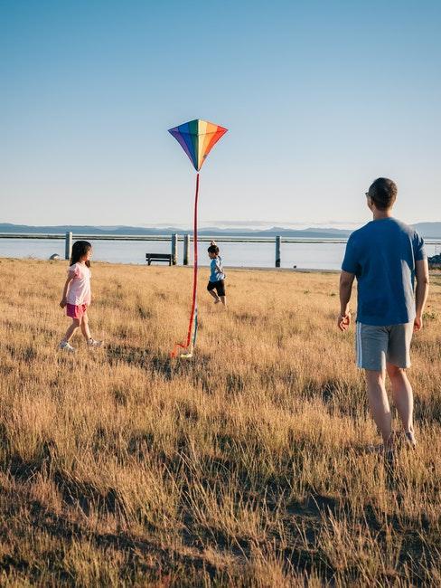 papa en train de jouer avec les enfants au cerf volant