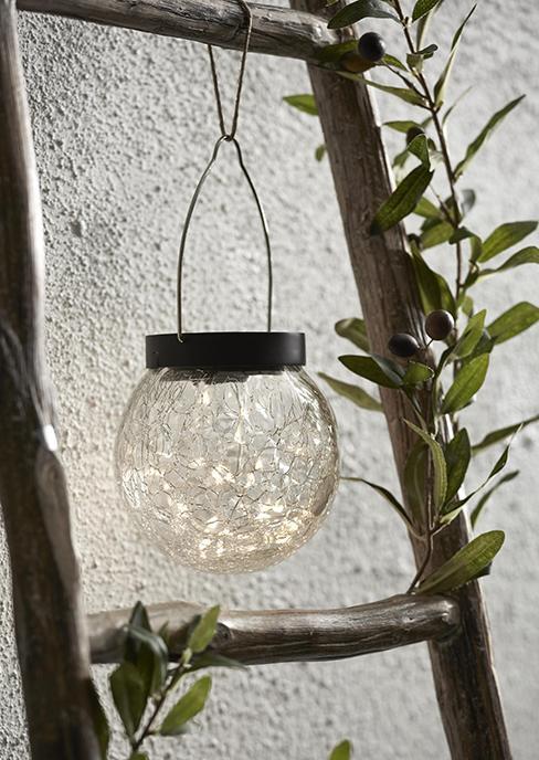 lampe solaire ronde accrochée à une échelle en bois