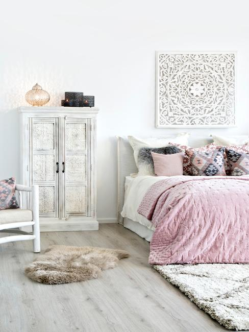 Chambre à coucher avec parquet gris, tapis blanc et lit avec couverture rose