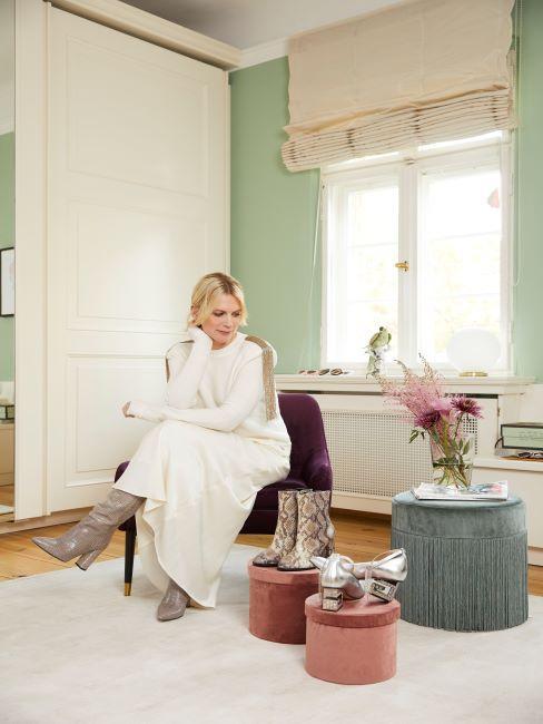 femme assise sur un pouf dans un salon pastel, mur vert, poufs sur lesquels sont posees les chaussures design