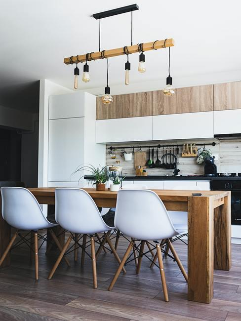 cuisine avec table en bois massif, chaises blanches avec pieds en bois, suspension avec barre en bois et ampoules nues, style scandinave, danois, hygge
