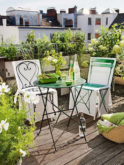 balcon avec sol en bois, chaises et table en métal vert, plantes de balcon