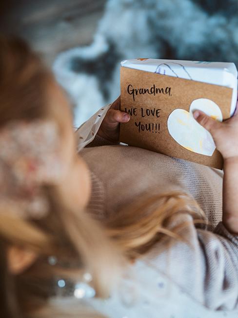 petit fille avec un livre dans ses mains pour la fête des grands mères