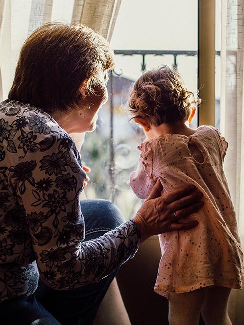 une mamie avec sa petite fille regardant par la fenêtre