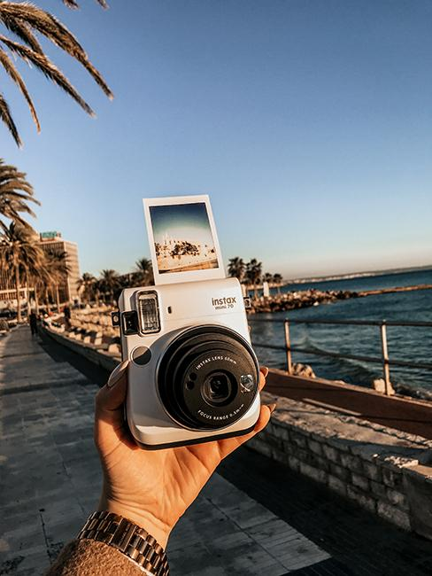 appareil photo polaroid tenu dans une main au bord de met