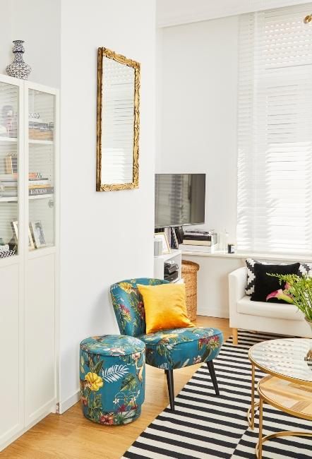 miroir doré style baroque dans appartement avec fauteuil vert