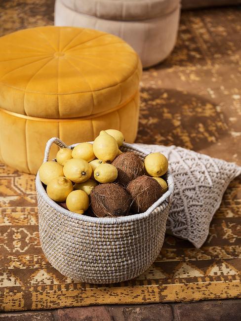 Pouf jaune foncé sur un tapis ochre devant un panier en cannage avec des citrons à l'intérieur