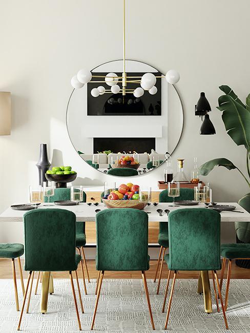 salle à manger avec chaises en vert et grand miroir rond