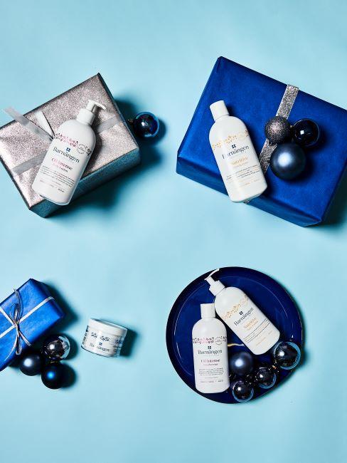 4 cadeaux emballes dans du papier bleu satine avec des cosmetiques poses dessus