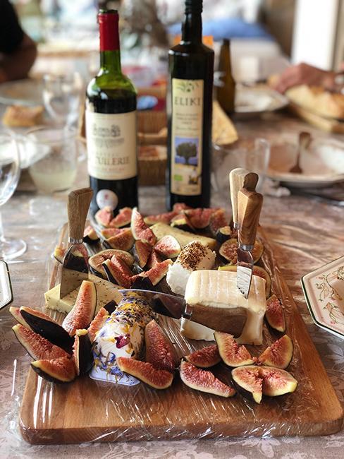 Plateau de fromages en bois avec fromages, figues et bouteilles de vin