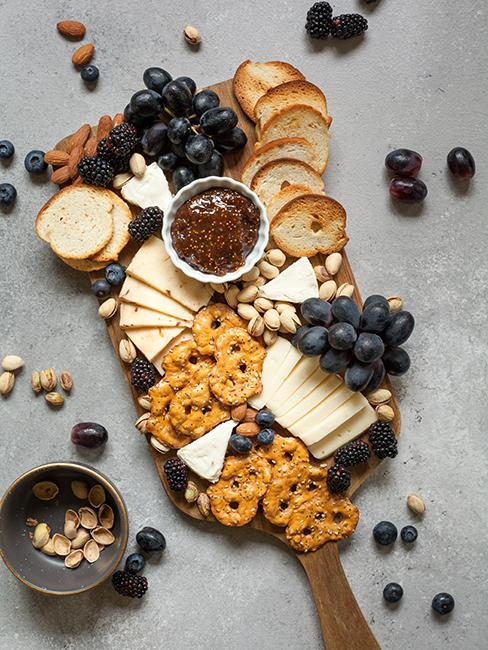 Plateau de fromages, avec crackers, raisins et confiture