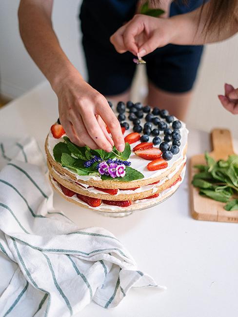 Personne entrain de préparer un gâteau avec des fruits frais