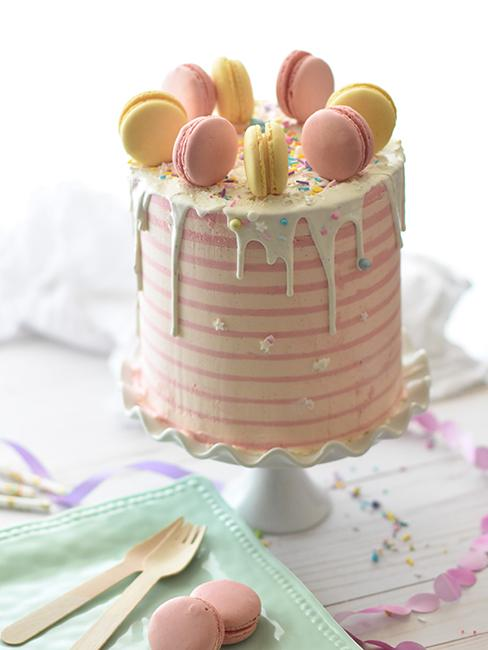 Layer cake blanc et rose pastel avec des macarons