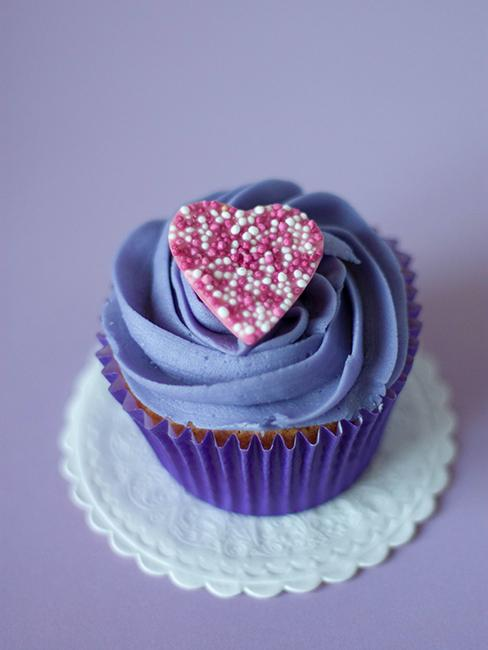 Cupcake avec topping violet et coeur posé dessus