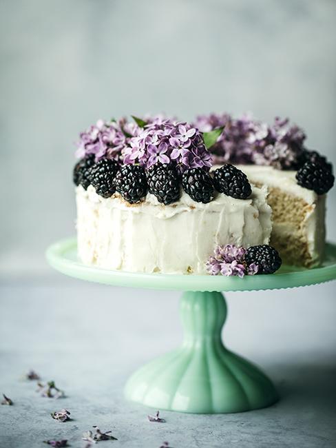Layer cake avec nappage au cream cheese, mûres et fleurs violettes pour la décoration