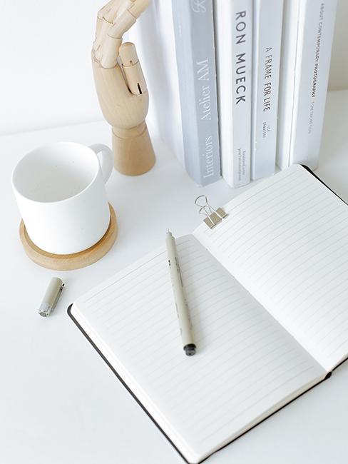 Carnet de notes sur une table blanche avec un style et une tasse