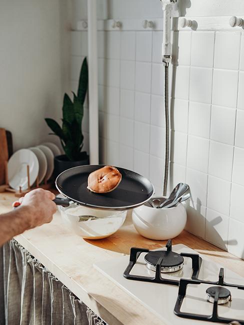 Une personne entrain de cuire un pancake dans une poel